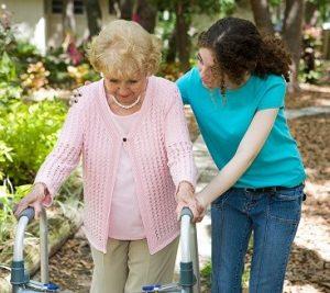 Seniorin läuft mit ihrem Rollator und wird von Betreuungsperson unterstützt